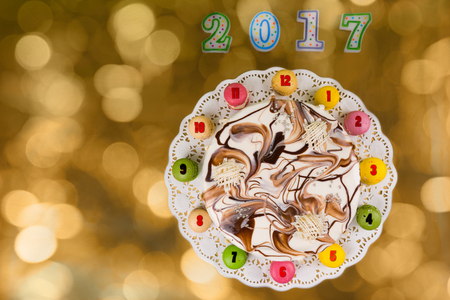 sweet seventeen: New year cake and macarons as a clock near candles number 2017 on bright colorful background, new year concept Stock Photo