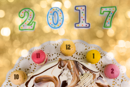 sweet seventeen: Cake and macarons as a clock near candles number 2017 on bright colorful background, new year concept Stock Photo