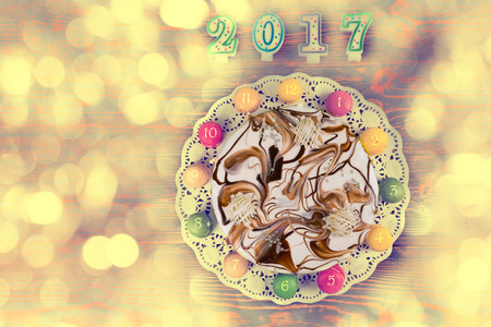 sweet seventeen: New year cake and macarons as a clock near candles number 2017 on colorful background, new year concept