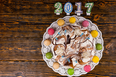 sweet seventeen: New year cake with lots of candles and macarons near candles number 2017 on wooden background, new year concept Stock Photo