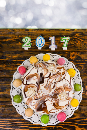 sweet seventeen: Cake for new year and christmas on wooden background, near candles number 2017, new year concept