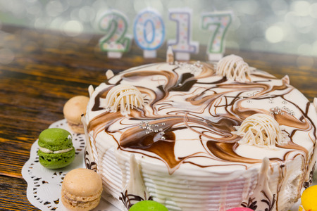 Cake for new year and christmas on wooden desk, candles number 2017 on background, new year concept