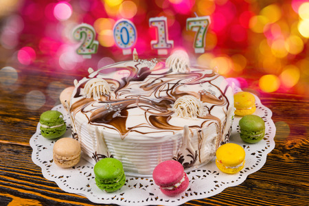 sweet seventeen: Cake for new year with candles number 2017 on wooden desk, bright pink and red lights on background, new year concept Stock Photo