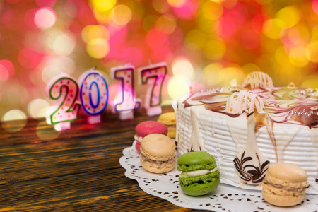 sweet seventeen: Cake for new year and christmas with macarons on wooden desk, candles number 2017 on background, new year concept Stock Photo