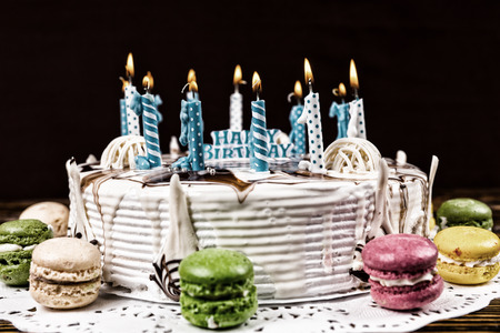 White appetizing birthday cake with lots of burning candles near different colored macarons