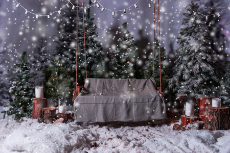 flashlights: Empty wooden swing with a blanket above the flashlights in a snow-covered park or a forest with spruce trees and stumps with big beautiful candles Stock Photo