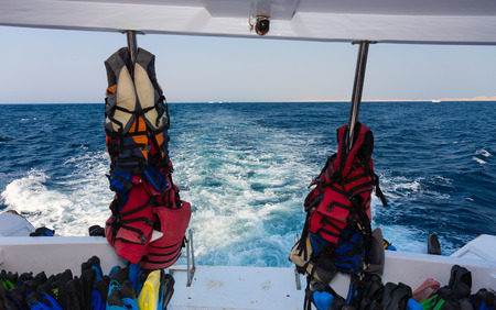 Lifejackets and other equipment for diving on back teak deck of a motor yacht