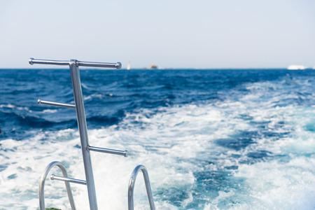 Metal steel ladders on back teak deck of a motor yacht sailing on a sea