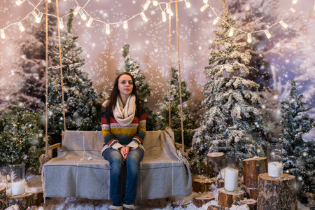 flashlights: Happy female sitting on a bench or a swing above the flashlights in a snow-covered park with spruce trees and stumps with big beautiful candles, wearing warm woolen sweater and knitted scarf while snowing Stock Photo