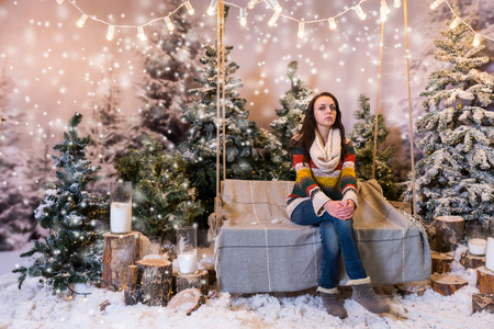 flashlights: Young beautiful female sitting on a bench or a swing above the flashlights in a snow-covered park with spruce trees and stumps with big beautiful candles, wearing warm woolen sweater and knitted scarf while snowing