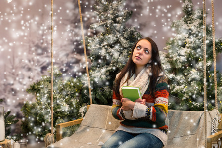 Attractive girl dreaming while sitting on a swing with a blanket and holding a book in a snow-covered park with spruce trees, wearing warm woolen sweater and knitted scarf while snowing