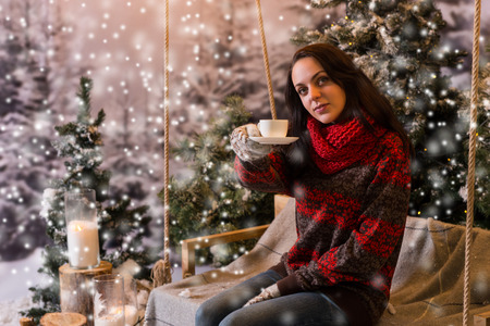 snowcovered: Young female sitting on a swing with a blanket under the flashlights and offering a cup of coffee in a snow-covered park with spruce trees, wearing red woolen sweater and knitted scarf while snowing