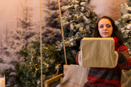 snowcovered: Woman sitting on a swing with a blanket under the flashlights and offering a box with a present in a snow-covered park with spruce trees, wearing red woolen sweater and knitted scarf