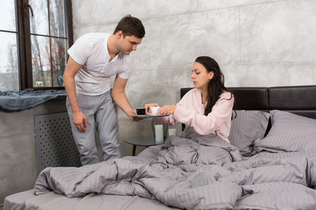 Young man brought coffee in bed while his wife sitting in the bed wearing pajama in the bedroom in loft style