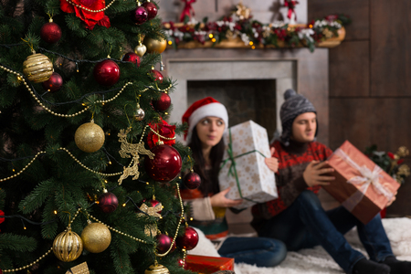 Cute young couple guessing at their Christmas gifts holding a boxes to his ears as they shake it while sitting on a rug in front Christmas tree