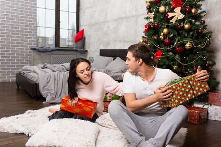 wants: Young woman wants to see her boyfriends gift, but he hides it while sitting on the carpet near Christmas tree in the room in loft style Stock Photo