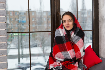 dreaminess: Young smiling woman wrapped in a blanket while sitting on the windowsill in the living room