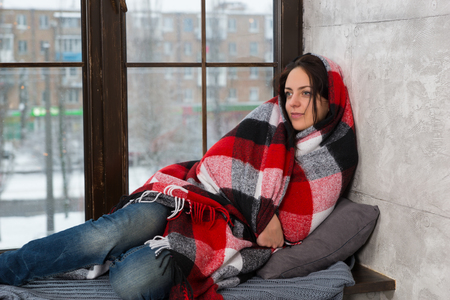 Young smiling woman wrapped in a blanket while lying down on the windowsill in the living room