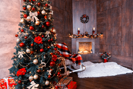 Comfortable living room with rocking chair with a blanket, decorated modern flaming fireplace and large Christmas tree with a lot of presents and different decorations Stock Photo