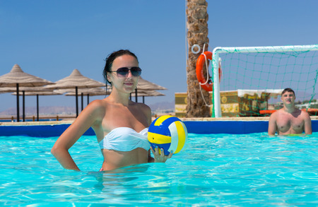 Young athletic woman holding a ball while playing water polo at the hotel on a sunny summer day