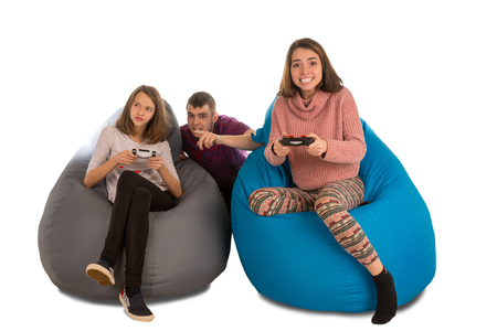 Young people are enthusiastic about playing video games while sitting on blue and grey beanbag chairs for living room or other room isolated on white background