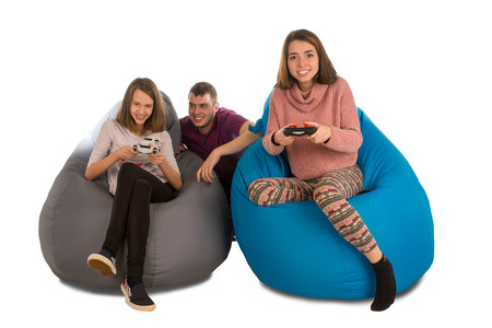 Young happy people are enthusiastic about playing video games while sitting on blue and grey beanbag chairs for living room or other room isolated on white background