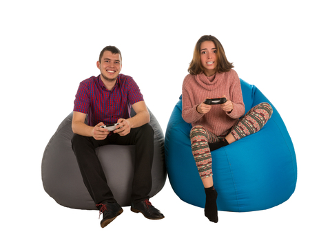 Young attractive man and woman sitting on blue and grey beanbag chairs for living room or other room and playing video games isolated on white background Stock Photo