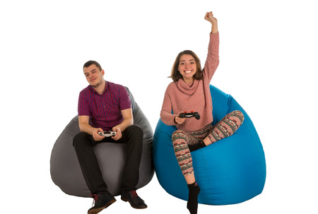 Young man and woman are enthusiastic about playing video games while sitting on blue and grey beanbag chairs for living room or other room isolated on white background