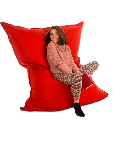 Pretty young woman sitting on red beanbag sofa chair for living room or other room and holding a book isolated on white background