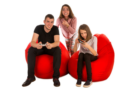 Young funny people are enthusiastic about playing video games while sitting on red beanbag chairs isolated on white background