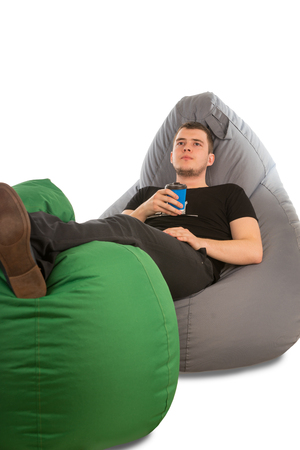 Young pensive man lying on beanbag chairs and holding coffee isolated on white background