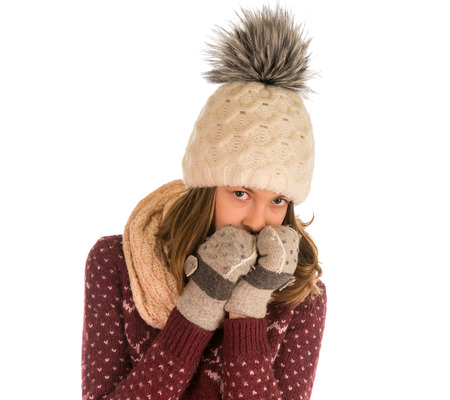 Cute girl in sweater, hat, scarf and mittens covered her face isolated on white background