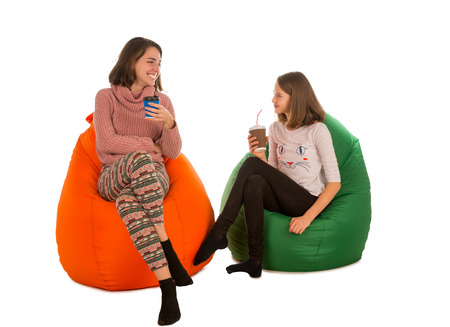 Stock Photo   Young Woman And Smiling Girl Sitting On Beanbag Chairs And  Drinking Coffee Isolated On White Background