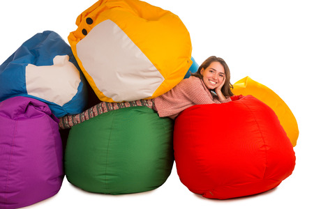 Young Smiling Woman Lying Between Beanbag Chairs Isolated On White  Background
