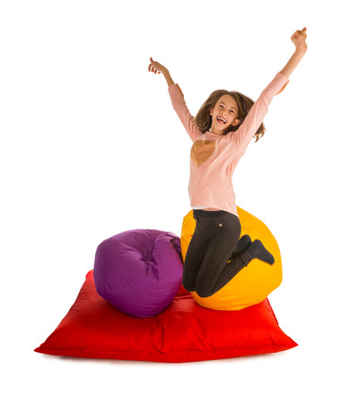 Happy girl jumping near beanbag chairs and beanbag sofa isolated on white background