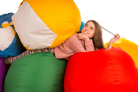 Young dreaming woman lying between beanbag chairs isolated on white background