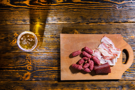near beer: High angle view of cutting board with sausages, bacon and meat on wooden table near a glass of beer