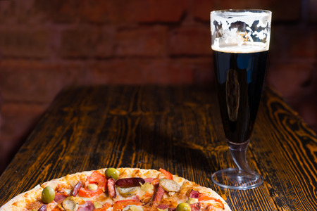 near beer: Pizza with variety of toppings and cheese on wooden table near a glass of dark beer Stock Photo