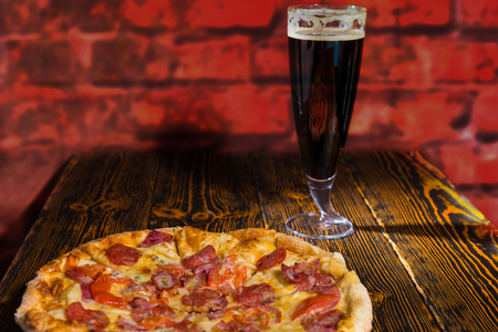 near beer: Tasty pepperoni pizza with variety of toppings and cheese on wooden table near a glass of dark beer