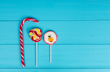 Three colorful sugar lollipops on wooden turquoise table