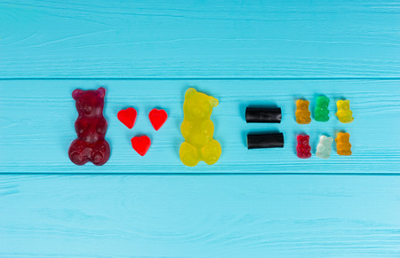 Tasty jelly candies represent that one big gummy bear plus a second equals a lot of little bears on wooden turquoise table