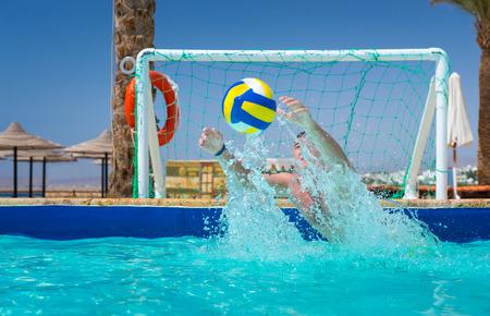 Man probeert om de bal in het zwembad te vangen, spelen waterpolo in het hotel op een zonnige zomerdag