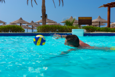 Young man swimming and trying to catch the ball in a pool at the hotel on a sunny summer day