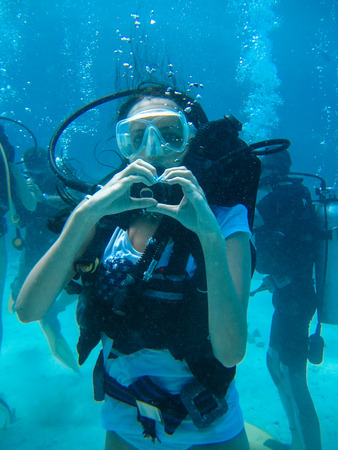 deepness: Underwater shoot of a woman diving with scuba and showing love signal