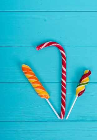 Tasty candy cane and colorful bright lollipops on wooden turquoise board Stock Photo