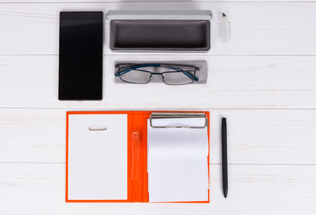 Open diary with a pen for organising a schedule, stylish glasses and open case for glasses near mobile phone on wooden white table