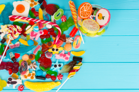 View from above on cattered jelly candies near glass can with chewing sweets on wooden turquoise board