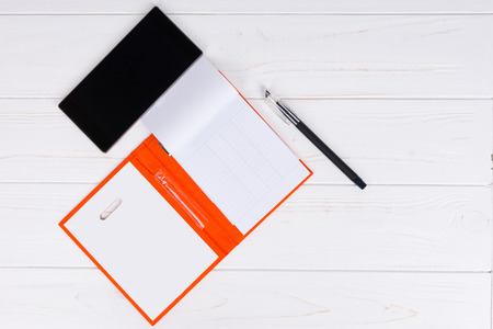 Open blank page of an orange diary with a pen for making appointments, organising a schedule and mobile phone on wooden white table Stock Photo