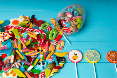 View from above on cattered candies and lollipops as fruits near glass can with chewing sweets on wooden turquoise board