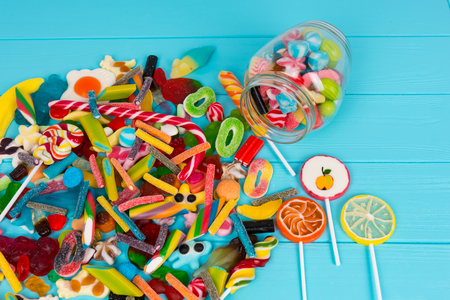Cattered candies and lollipops as fruits near glass can with chewing sweets on wooden turquoise board